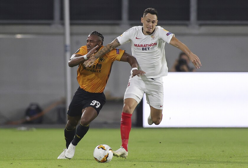 Wolverhampton Wanderers' Adama Traore, left, challenges for the ball with Sevilla's Lucas Ocampos during the Europa League quarterfinal soccer match between Wolves and Sevilla at the MSV Arena in Duisburg, Germany, Tuesday, Aug. 11, 2020. (Friedemann Vogel, Pool Photo via AP)