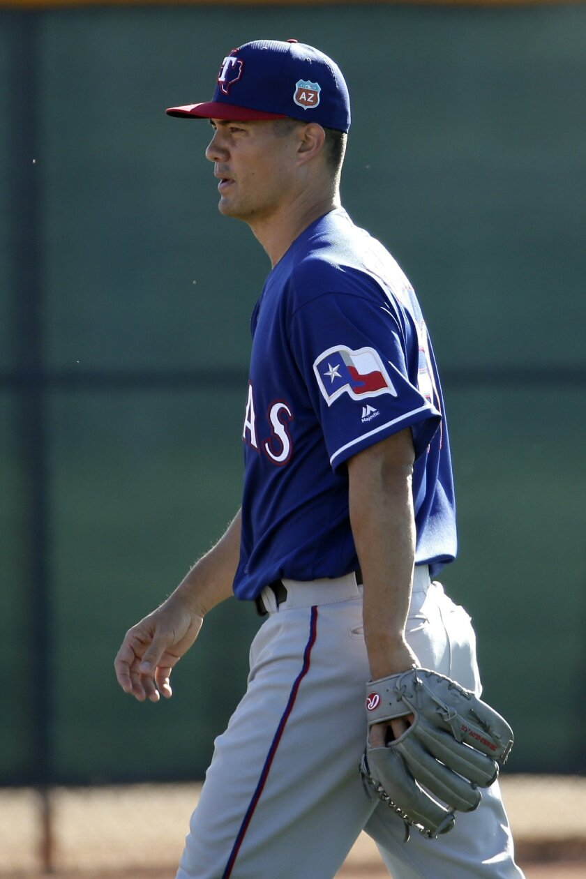 FILE - In this Feb. 21, 2016, file photo, Texas Rangers pitcher Jeremy Guthrie walks between drills during spring training baseball practice, in Surprise, Ariz. Jeremy Guthrie knows that feeling of things being the same but different. The right-hander is still in Surprise for spring training, now with the Rangers instead of on the other side with the World Series champion Royals.(AP Photo/Charlie Riedel, File)