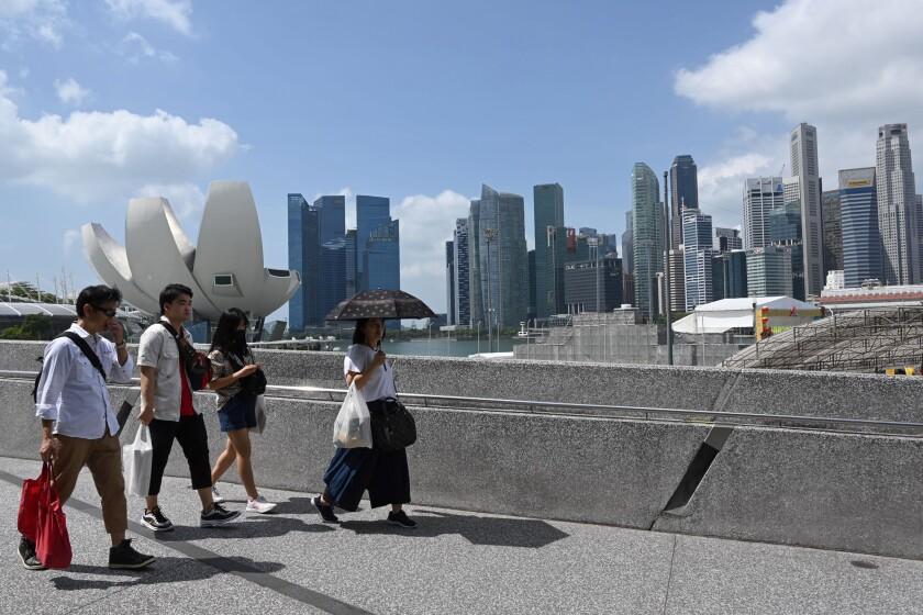 People walk past Marina Bay Sands resort in Singapore
