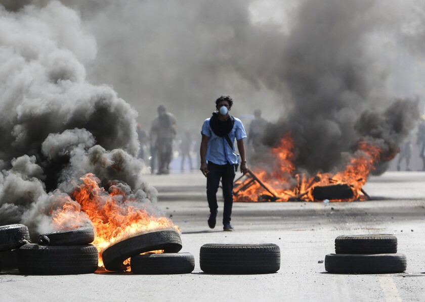 A protester walks between burning barricades in Managua, Nicaragua, in 2018.