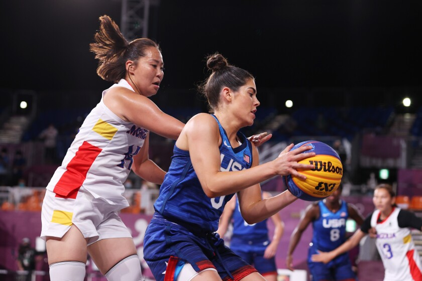 Kelsey Plum of Team United States is challenged by Solongo Bayasgalan of Team Mongolia in the Tokyo Olympics.