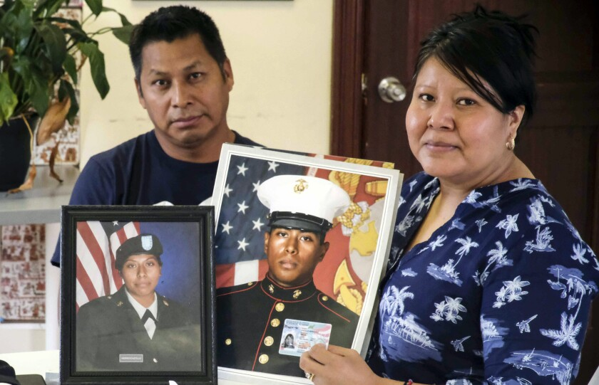 Imelda Castillo Hernandez and her husband, Artemio Rosales, hold pictures of their children Keila Nayeli Manchester and Frank Hebreo. The Staten Island mother of five became a permanent U.S. resident this week, in part due to the military service of her two eldest children.