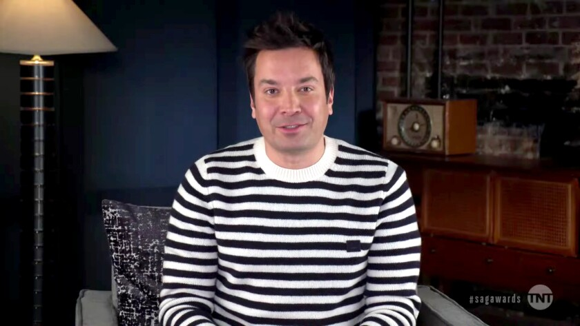 Jimmy Fallon sits in his basement, wearing a blue and white striped sweater.