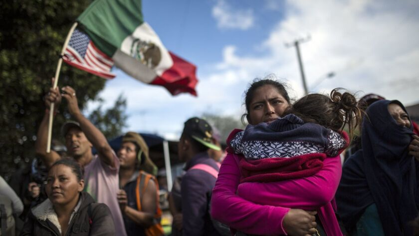 Honduran migrant Leticia Nunes holds her daughter Mailyn as she stands with a small group of other m