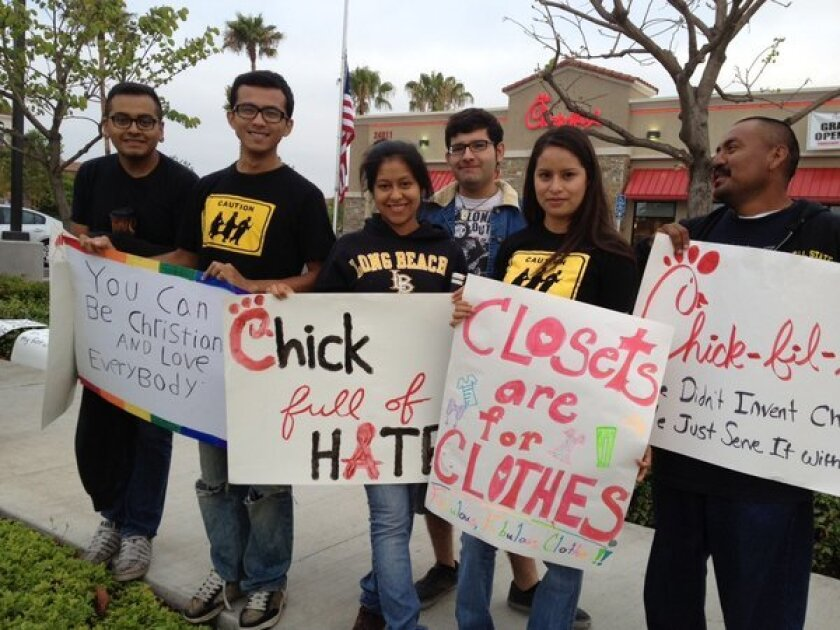 Teens protest outside the new Laguna Hills Chick-fil-A, which opened Thursday.