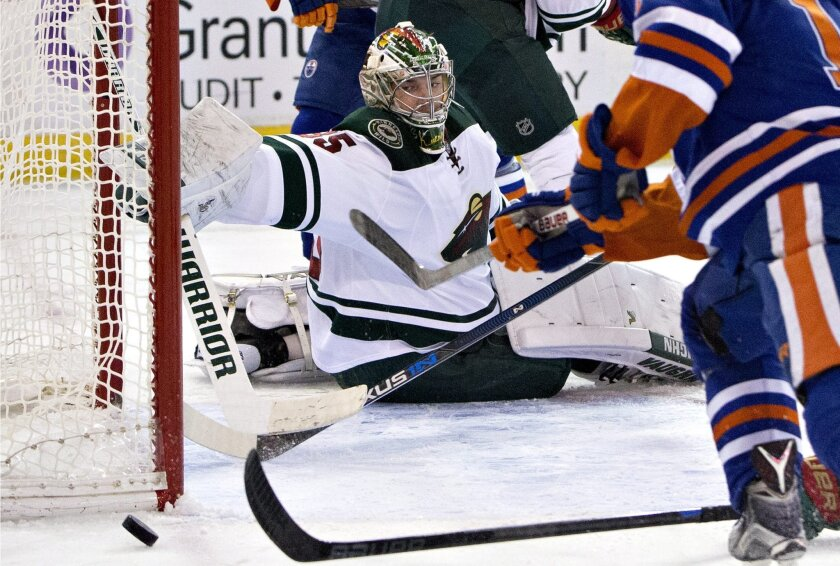 Minnesota Wild goalie Darcy Kuemper (35) reaches for the loose puck during the second period against the Edmonton Oilers in an NHL hockey game Thursday, Feb. 18, 2016, in Edmonton, Alberta. (Jason Franson/The Canadian Press via AP)