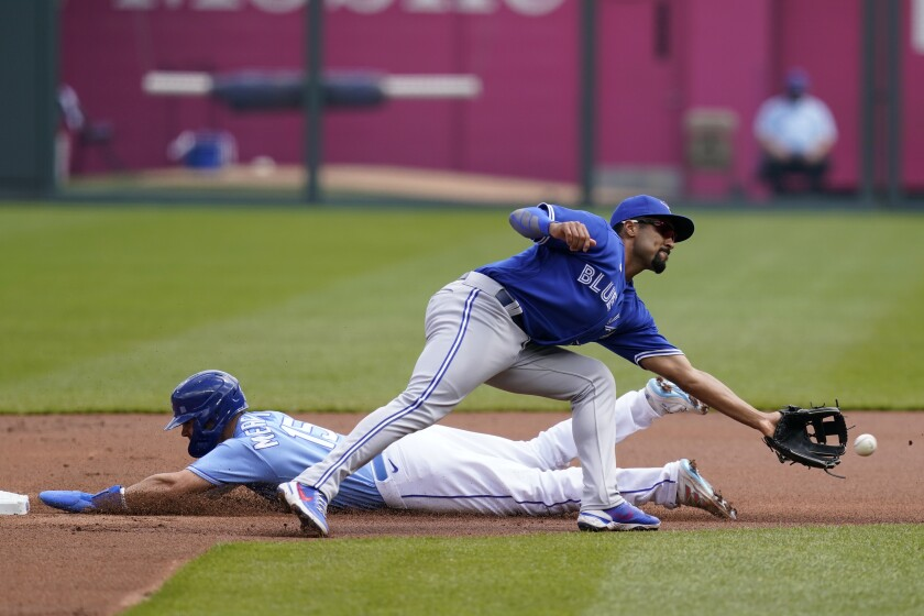 Kansas City Royals Whit Merrifield, left, steals a base behind Toronto Blue Jays second baseman Marcus Semien, right, during the first inning of a baseball game at Kauffman Stadium in Kansas City, Mo., Sunday, April 18, 2021. (AP Photo/Orlin Wagner)