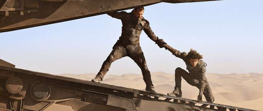 """Two men cling to a futuristic craft in the movie """"Dune."""""""