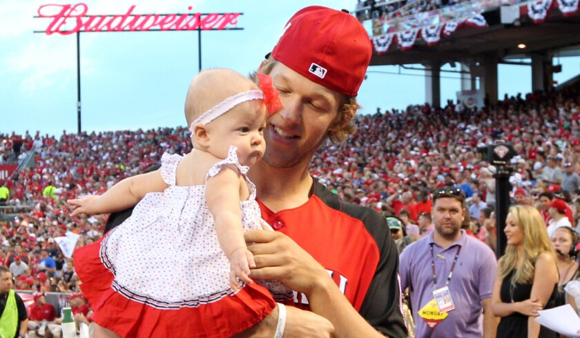Clayton Kershaw holds his daughter while walking on the sidelines during the Home Run Derby at Great American Ball Park in Cincinnati on July 13, 2015.