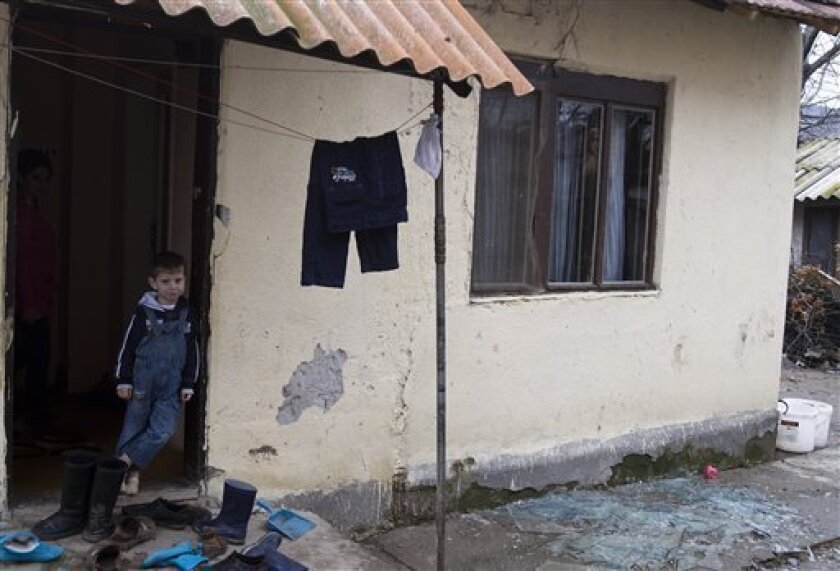 Nenad Masic, 4-years old stands near shattered glass caused by hand grenades thrown at his house in the ethnically tense town of Mitrovica on Thursday, Feb. 19, 2013. Nobody was hurt in the blast.  Kosovo officials say a series of hand grenade attacks in Kosovo's north are aimed at derailing effort