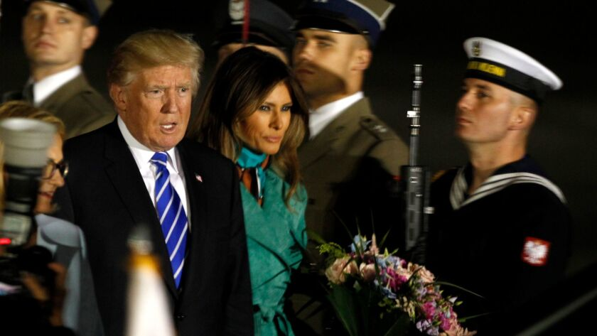 President Trump, right and the first lady Melania Trump walk past the honor guards as they arrive to