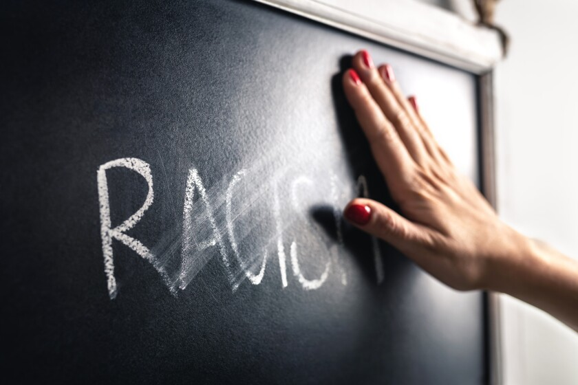 Racism concept. Stop hate and discrimination. Against prejudice and violence. Hand wiping off and erasing the word from blackboard.