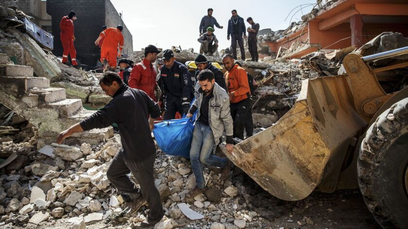 MOSUL, NINEVEH PROVINCE -- FRIDAY, MARCH 24, 2017: With the help of family members, Iraqi civil defe