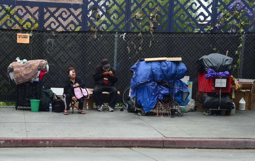 Homeless residents sit with their belongings in downtown Los Angeles.