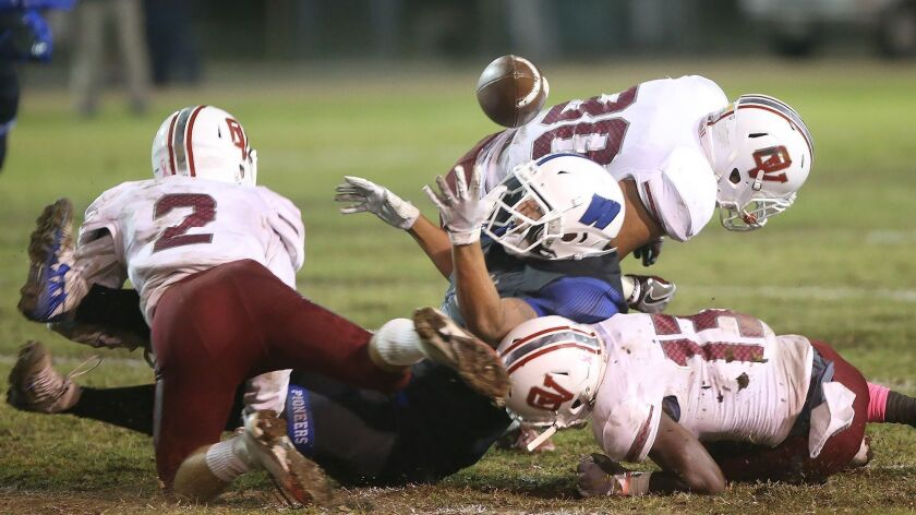 Ocean View defense of Will Earthman (2) and Raelen Bruce (13) force a fumble from Western High's #5
