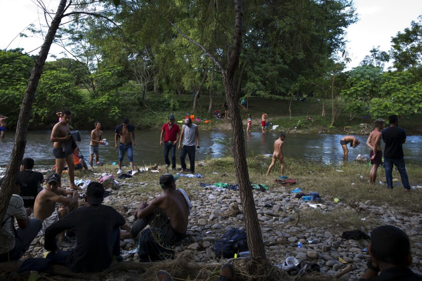 Migrants, who are part of a caravan of Central Americans trying to reach the U.S. border, bathe and wash clothes in the Novillero River in Tapanatepec, Mexico,
