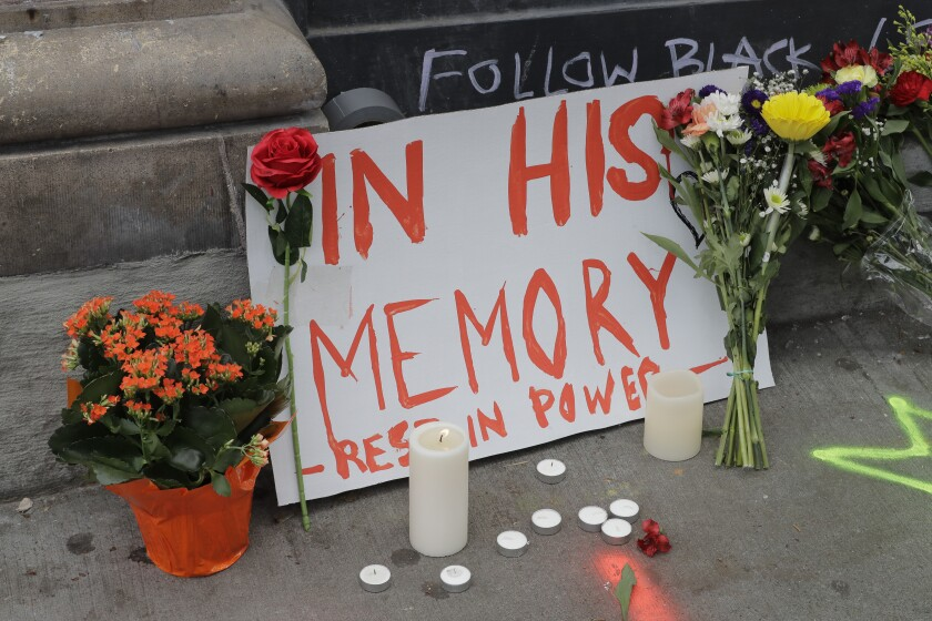 """A sign that reads """"In his Memory Rest in Power,"""" is displayed at a growing memorial to a person named Lorenzo, Saturday, June 20, 2020, at the intersection of 10th Ave. and Pine St. near the Capitol Hill Occupied Protest zone in Seattle. A pre-dawn shooting near the area left one person dead and critically injured another person, authorities said Saturday. The area has been occupied by protesters after Seattle Police pulled back from several blocks of the city's Capitol Hill neighborhood near the Police Department's East Precinct building. (AP Photo/Ted S. Warren)"""