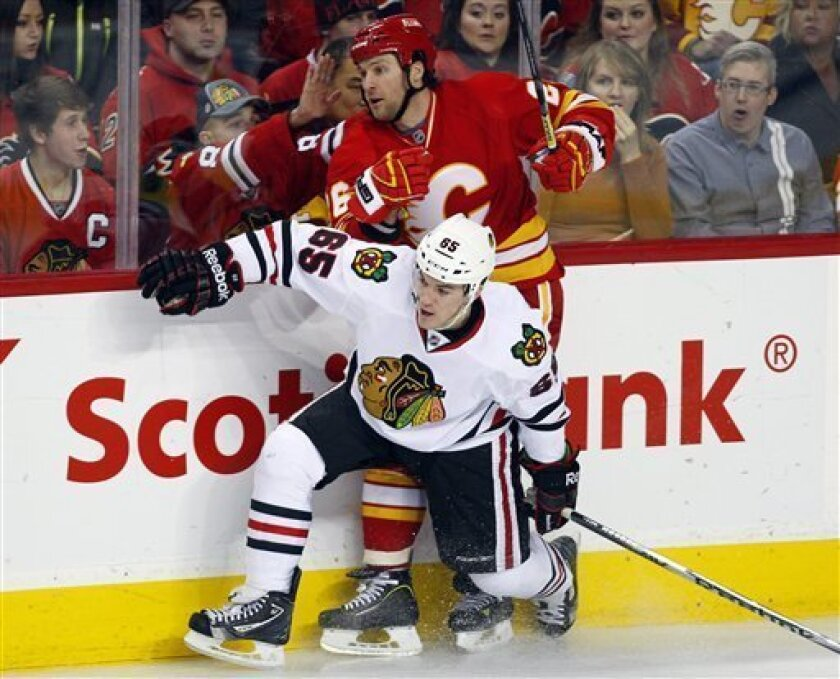 Chicago Blackhawks' Andrew Shaw (65) checks Calgary Flames' Dennis Wideman during first-period NHL hockey game action in Calgary, Alberta, Saturday, Feb. 2, 2013. (AP Photo/The Canadian Press, Jeff McIntosh)