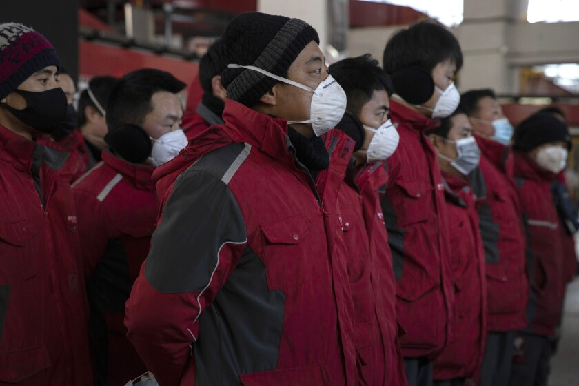 Drivers for Chinese e-commerce giant JD.com wear masks as they prepare for morning deliveries in Beijing on Tuesday.