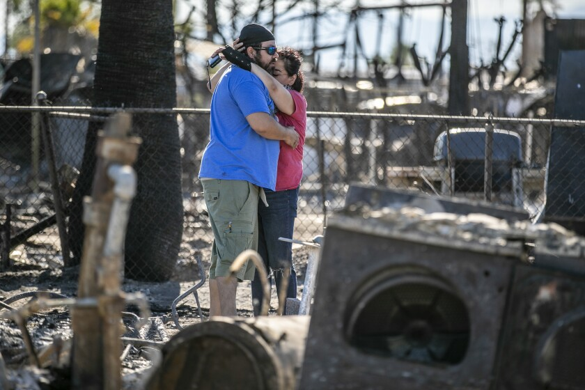 Guadalupe and Daniel Altamirano comfort each other as they survey the ashes of their cousin's home in Niland, Calif.