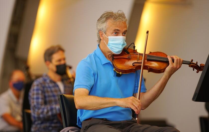 The concertmaster raises his violin.