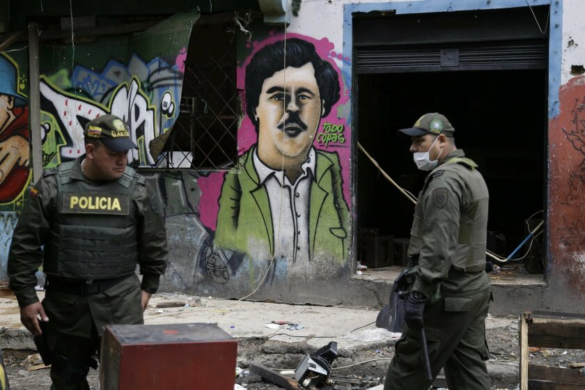 Police officers stand in front of a mural depicting the late drug kingpin Pablo Escobar, in the area known as El Bronx in downtown Bogota, Colombia, Monday, May 30, 2016. Thousands of police officers accompanied by city officials raided early Saturday the area plagued by drug addicts and prostituti
