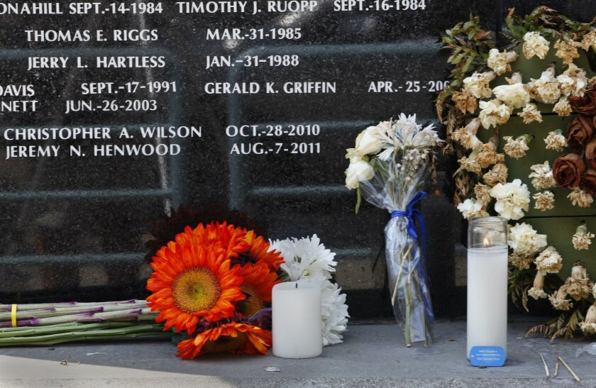 Flowers and candles were left at the San Diego Police Department memorial to officers who died in the line of duty after an officer-involved shooting left Jonathan DeGuzman dead and Wade Irwin wounded.|