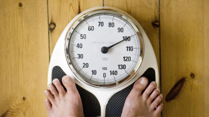 Man holding belly, with feet on weighing scales ORG XMIT: CHI1104011653043069 ** OUTS - ELSENT, FPG,