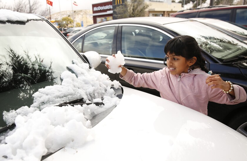 Vatsika Viswanathan, 8, grabs snow from the hood of a car