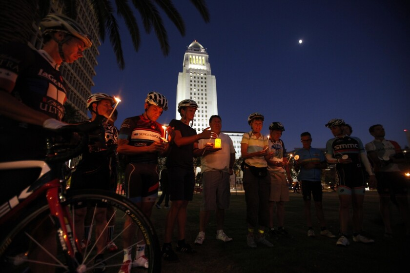 Cyclists hold a candlelight vigil for ex-Napster executive Milton Olin Jr. Deputy Andrew Francis Wood wasn't charged with killing Olin because police are exempt from a state law banning drivers from using wireless electronic devices.