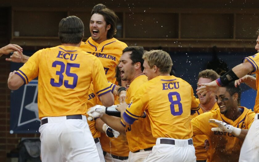 East Carolina catcher Travis Watkins, center, is mobbed by teammates after hitting the game-winning three run home run in an NCAA college regional tournament baseball game against Virginia in Charlottesville, Va., Saturday, June 4, 2016. East Carolina defeated Virginia 8-6. (AP Photo/Steve Helber)