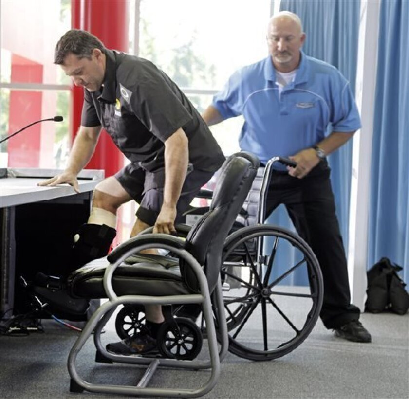 NASCAR driver and team co-owner Tony Stewart, left, arrives in a wheelchair assisted by Josh Katz, right, before a news conference at Stewart-Haas Racing's headquarters in Kannapolis, N.C., Tuesday, Sept. 3, 2013. (AP Photo/Chuck Burton)