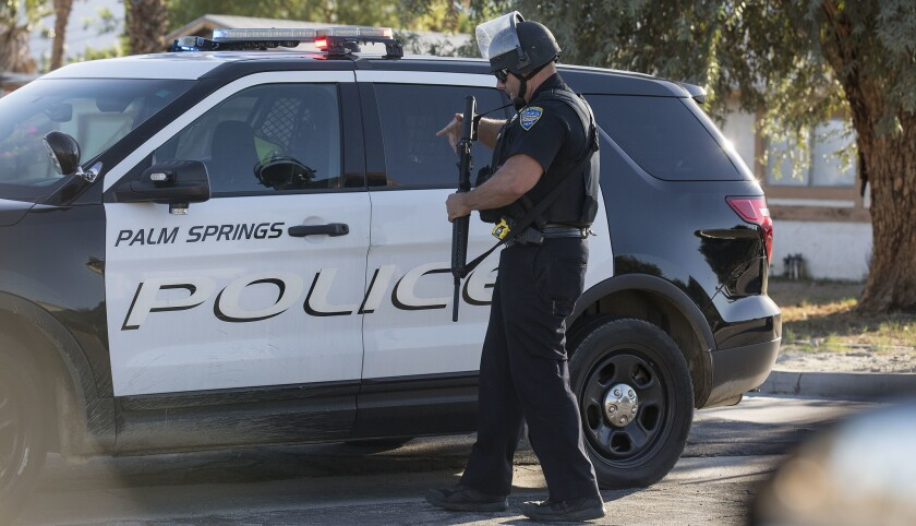 A Palm Springs police officer holding a shotgun next to a police SUV in 2016