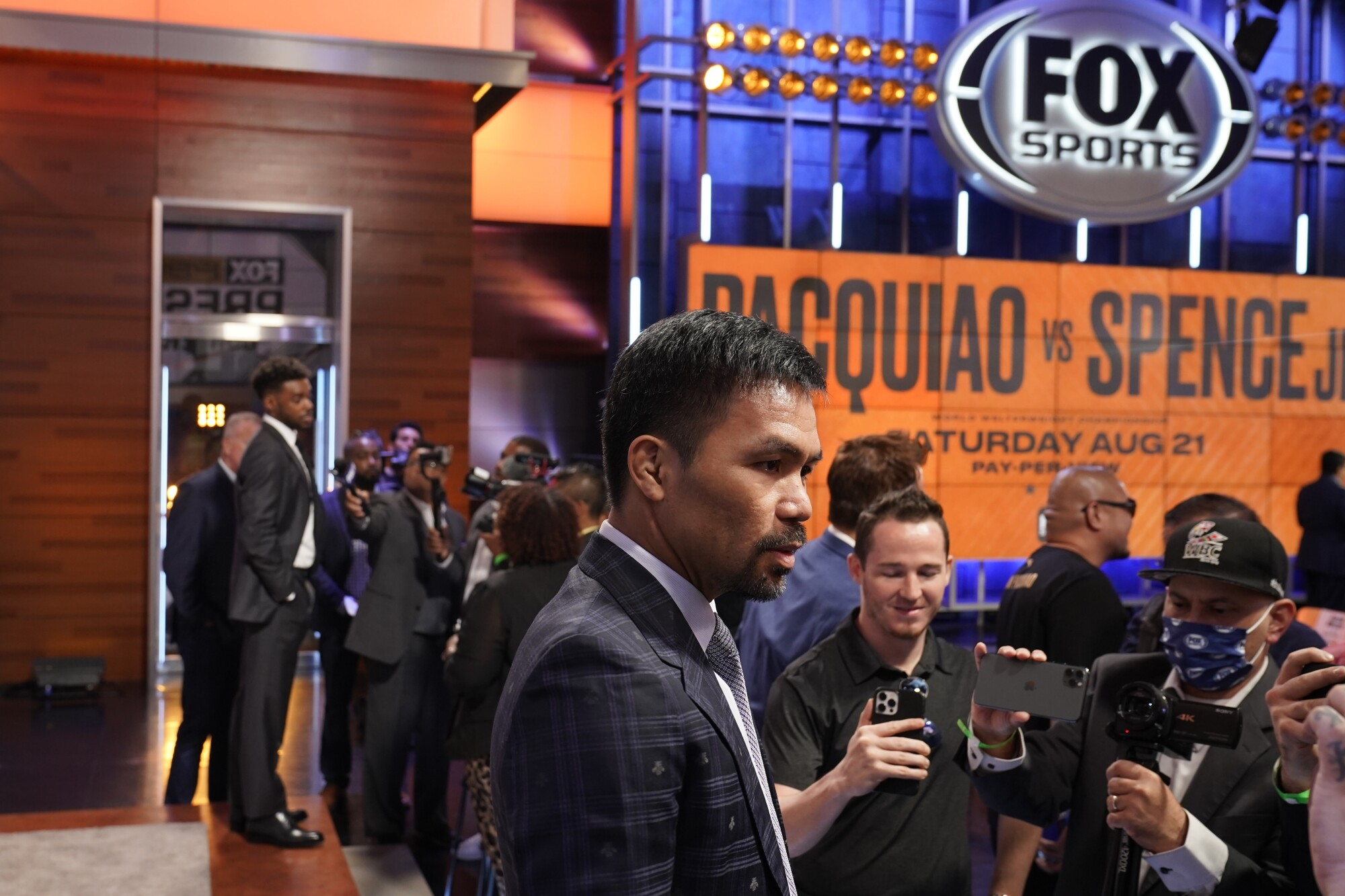 Boxers Manny Pacquiao, center, and Errol Spence Jr., far left, meet with reporters.