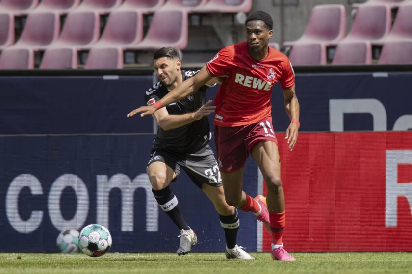 Kingsley Ehizibue del Colonia y Vincenzo Grifo del Freiburg pelean por el balón en el encuentro de la Bundesliga del domingo 9 de mayo del 2021. (Rolf Vennenbernd/dpa via AP)