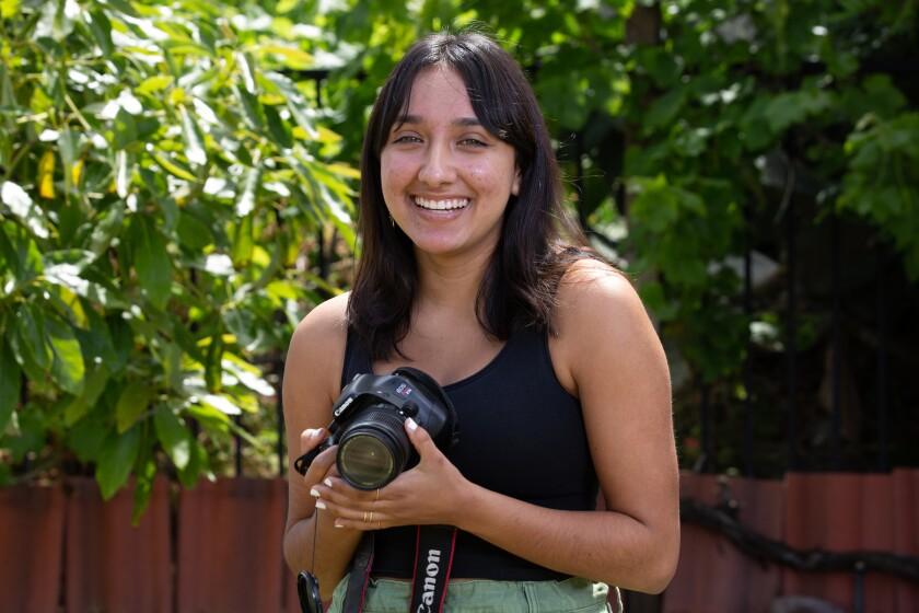 Maya Alfaro, a senior at Mira Mesa High School, standing outdoors holding a camera and smiling