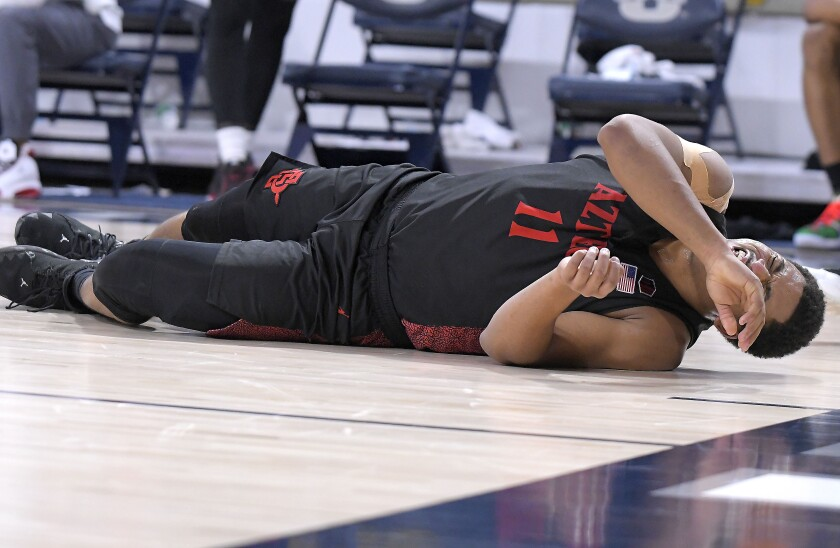 Matt Mitchell lies on the court after injuring his knee during the second half of Thursday's game at Utah State.