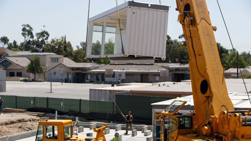 Construction workers use a crane to lift prefabricated classroom sections made of recycled shipping containers into position at Vaughn Next Century Learning Center.