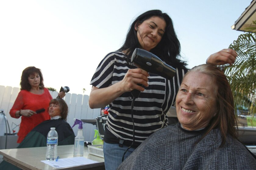 Volunteer hairstylist Carolina Martinez works on Donna, who is homeless and declined to give her last name. Martha Alboney (background) cuts and styles Elizabeth Flynn's hair.
