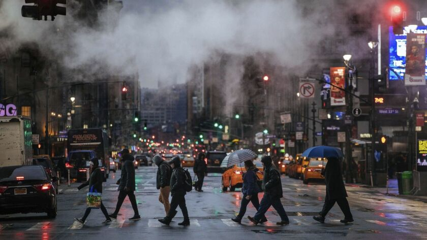 Pedestrians cross Seventh Avenue on Sunday, Jan. 20, 2019, in New York. The National Weather Service