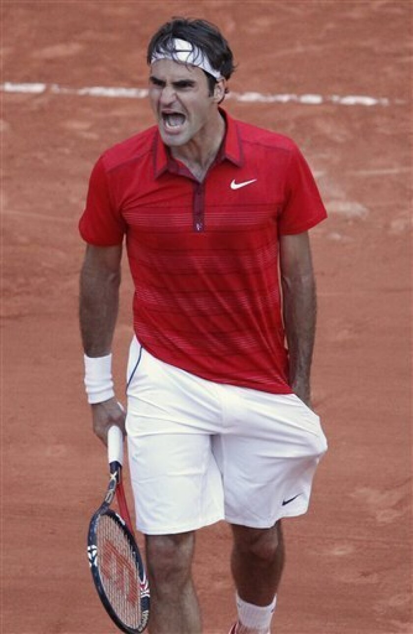 Roger Federer of Switzerland screams after defeating Novak Djokovic of Serbia in the semi final match of the French Open tennis tournament in Roland Garros stadium in Paris, Friday June 3, 2011. Federer won the match in four sets 7-6, 6-3, 3-6, 7-6. (AP Photo/Christophe Ena)