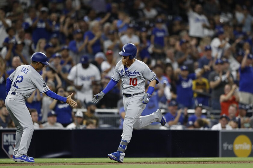Justin Turner is congratulated by Dodgers third base coach Dino Ebel after hitting a home run during the third inning Monday.