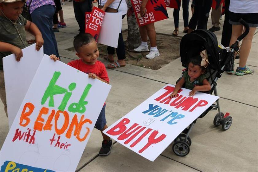 """Unos niños sostienen carteles donde se lee """"niños pertenecen a sus padres"""", durante una manifestación contra la separación de familias migrantes. EFE/Archivo"""