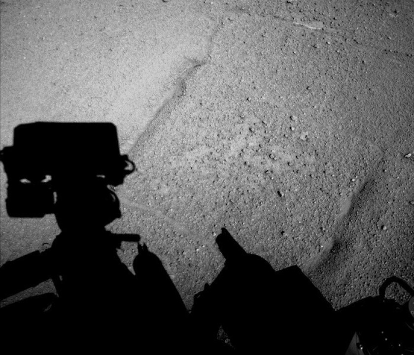 NASA's Mars rover Curiosity caught its own shadow in this image taken just after completing a backward drive of 329 feet Feb. 18. The rover drove the distance in reverse to test a method to reduce damage to its wheels.