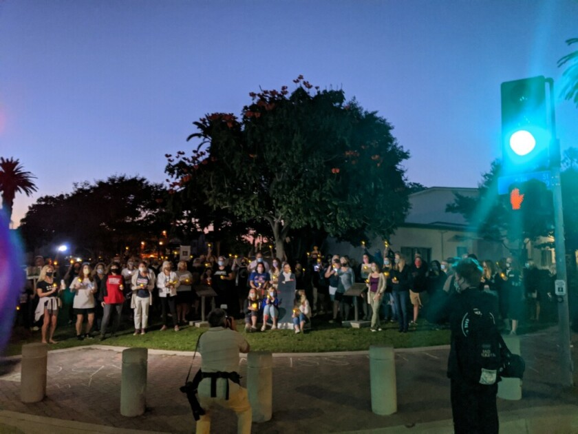People gather at Triangle Park in Huntington Beach at a candlelight vigil honoring Ruth Bader Ginsburg.