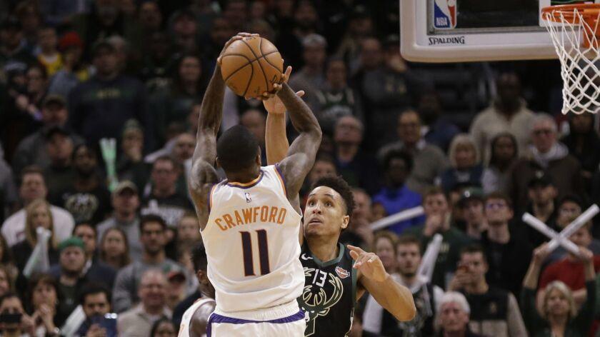 Phoenix Suns' Jamal Crawford (11) hits the game-winning shot over Milwaukee Bucks' Malcolm Brogdon.