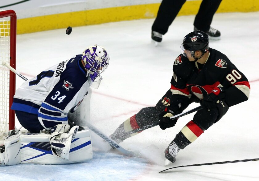 Winnipeg Jets goaltender Michael Hutchinson (34) stops a shot by Ottawa Senators' Alex Chiasson (90) during the first period of an NHL hockey game Thursday, Nov. 5, 2015, in Ottawa, Ontario. (Fred Chartrand/The Canadian Press via AP)