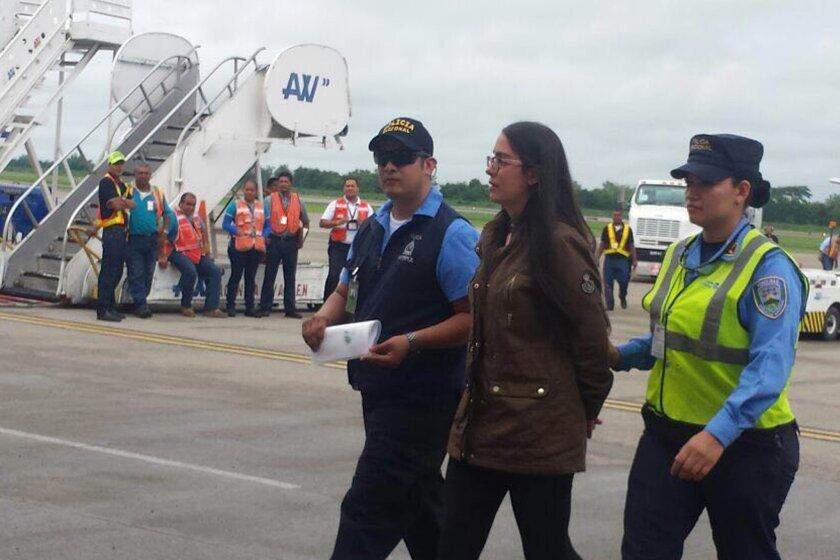 Fotografía cedida por la Agencia Técnica de Investigación Criminal (ATIC) de Honduras de la llegada al aeropuerto internacional Villeda Morales de San Pedro Sula, de la exmodelo hondureña Ilsa Vanessa Molina (c), deportada y detenida hoy, miércoles 22 de junio de 2016, por las autoridades. EFE/ATIC