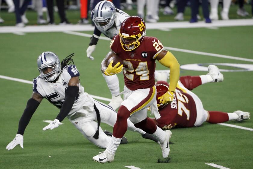 El corredor de Washington Antonio Gibson corre a la zona de anotación y supera al linebacker de los Cowboys