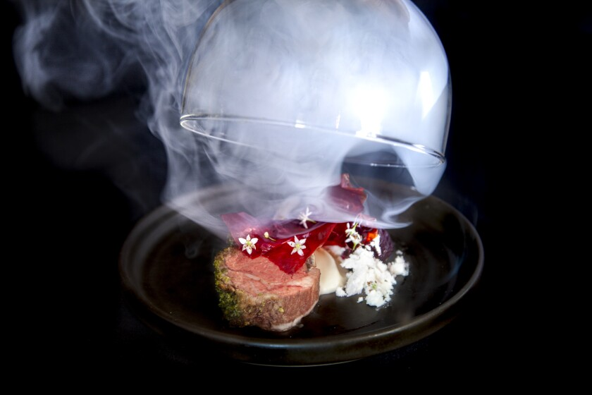 Sous-vide California lamb with beet glass, butter powder, blossoming onion and hickory rosemary smoke, one of the dishes on the new Avant Garde tasting menu at Rancho Bernardo Inn's Avant restaurant.